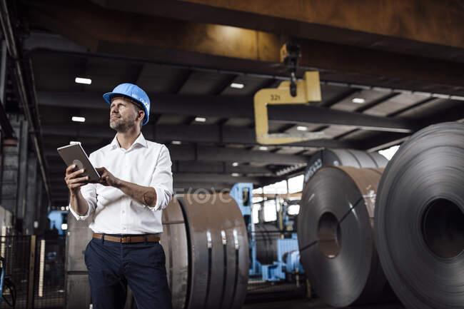Бізнесмен тримає цифрову табличку, дивлячись удалечінь стоячи на заводі. — стокове фото