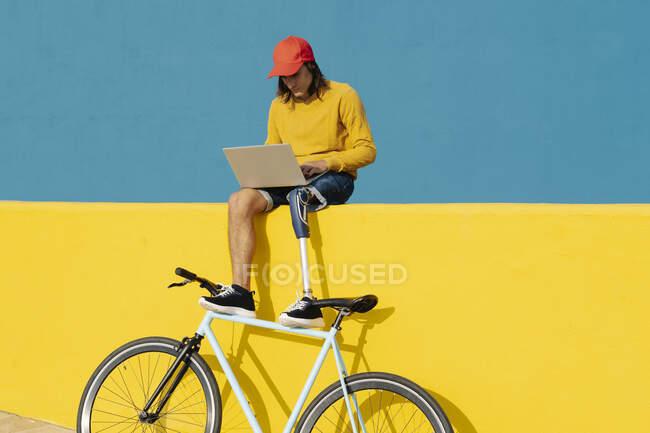 Hombre con extremidad artificial y pie trabajando en el ordenador portátil mientras está sentado en la pared multicolor - foto de stock