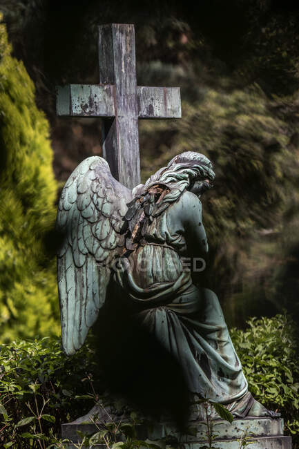 Estatua envejecida de ángel sentado al lado de la cruz en el cementerio - foto de stock