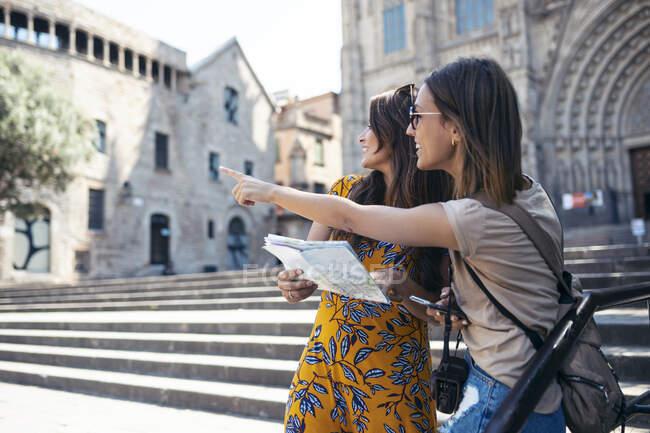 Amici che studiano mappa mentre si trovano in Piazza della Cattedrale di Barcellona, Catalogna, Spagna — Foto stock