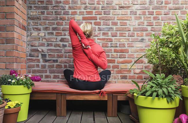 Mujer madura estirando las manos detrás de la espalda mientras hace ejercicio en el balcón - foto de stock