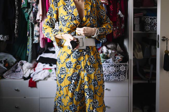 Média mulher adulta cinto de fixação em novo vestido amarelo no guarda-roupa em casa — Fotografia de Stock