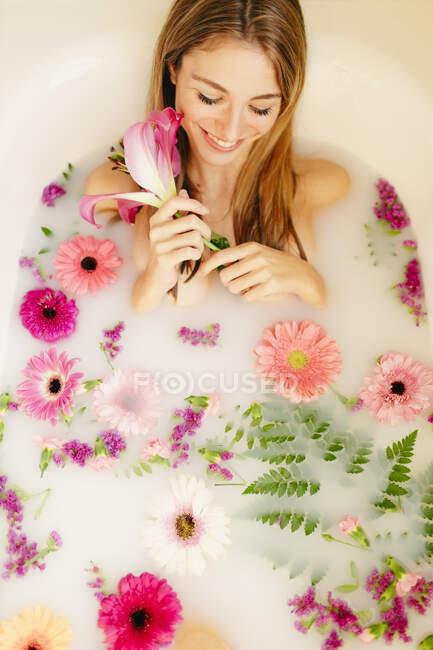 Smiling woman lying in bathtub while taking milkbath at spa - foto de stock