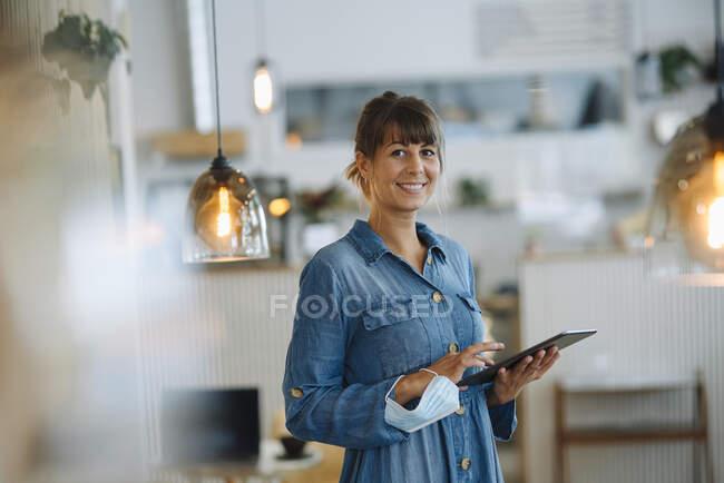 Жіночий підприємець використовує цифрову табличку, тримаючи захисну маску в кафе. — стокове фото
