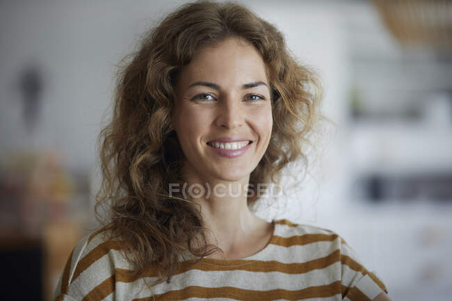 Красива жінка посміхається, стоячи вдома. — стокове фото