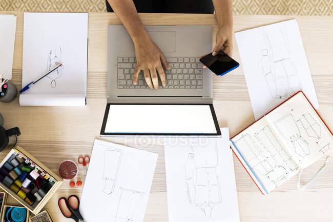 Diseñadora femenina usando portátil y teléfono inteligente en el estudio - foto de stock