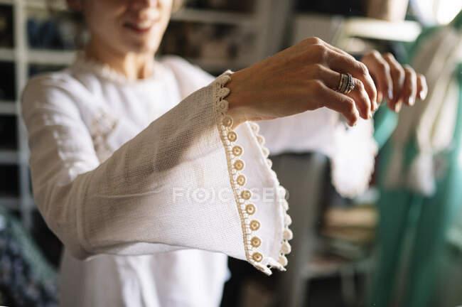 Mujer vistiendo nuevo vestido blanco con manga larga en el armario en casa - foto de stock
