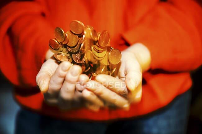 Adolescente chica de pie y lanzando moneda de euro con las manos ventosas - foto de stock