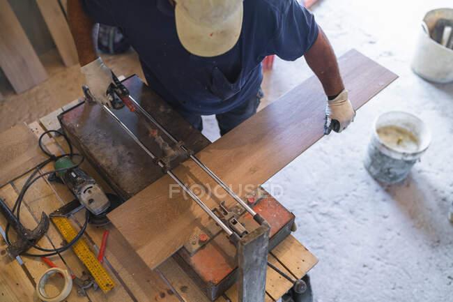 Hochwinkelblick eines reifen Mannes, der Parkettboden schneidet — Stockfoto