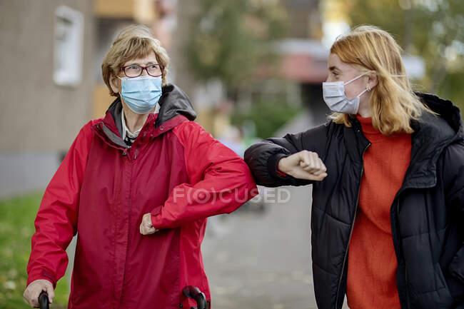 Nieta y madre con mascarilla facial saludando con codo mientras están de pie al aire libre - foto de stock