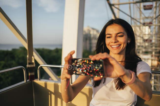 Happy woman using mobile phone on Ferris wheel at amusement park — Foto stock