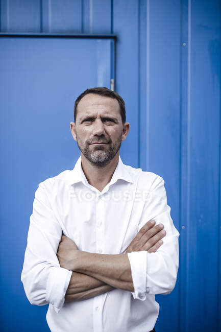 Businessman with arms crossed standing against metal wall — Stock Photo