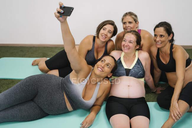 Группа беременных женщин делает селфи на смартфоне, сидя в студии йоги — стоковое фото