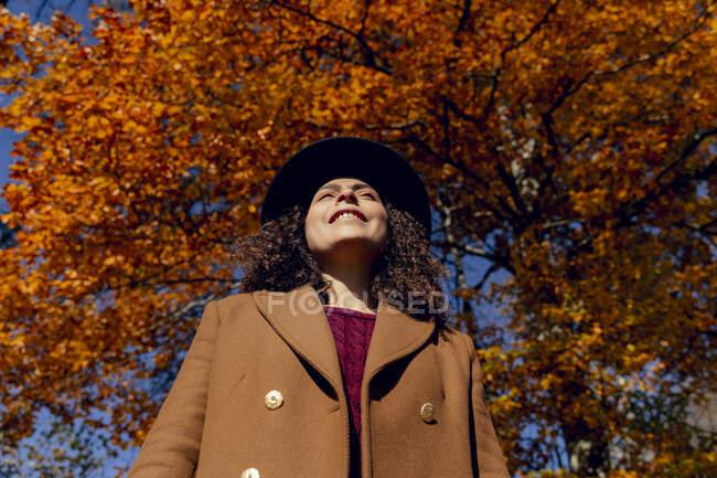 Mujer sonriente con sombrero bajo el árbol en el bosque - foto de stock