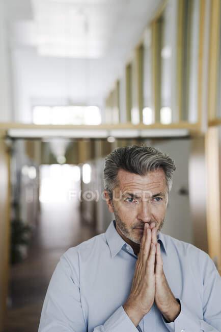 Geschäftsmann mit gefalteten Händen steht auf Büroflur — Stockfoto