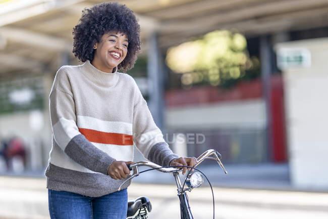 Jovem alegre que roda bicicleta enquanto olha para longe na estação ferroviária — Fotografia de Stock
