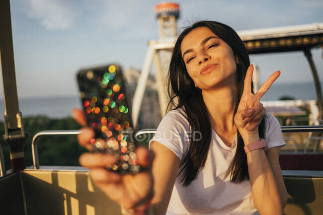 Beautiful young woman taking selfie through mobile phone while puckering and gesturing peace sign on Ferris wheel — Foto stock