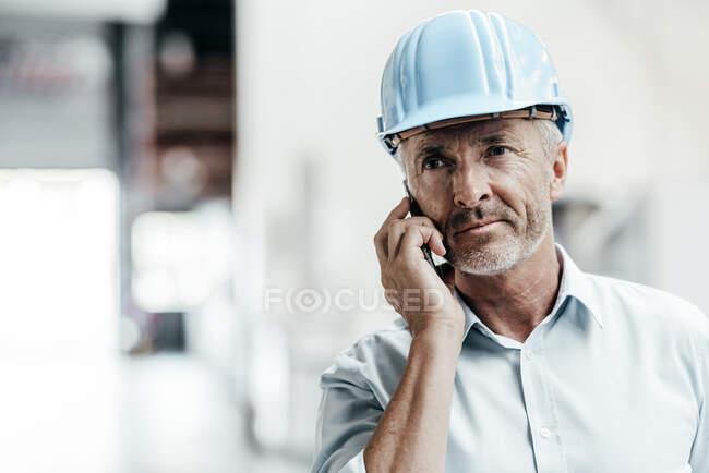 Ingeniero masculino maduro en hardhat mirando hacia otro lado mientras que habla en el teléfono móvil en fábrica - foto de stock