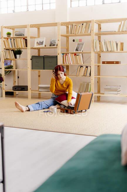 Junge Frau mit Kopfhörer hört Musik, während sie zu Hause Plattenspieler benutzt — Stockfoto