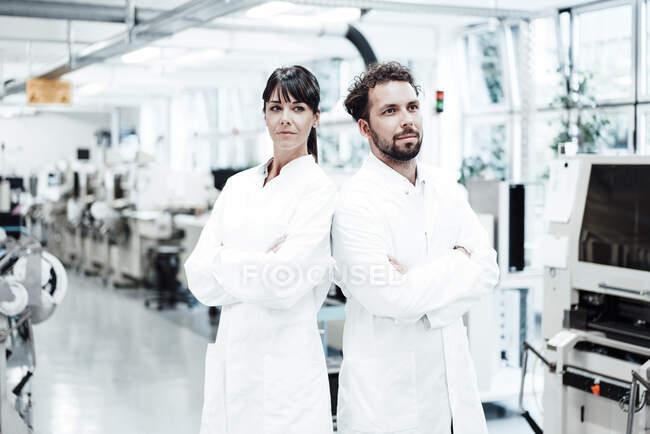 Scientifiques féminins et masculins confiants, bras croisés dans un laboratoire lumineux — Photo de stock