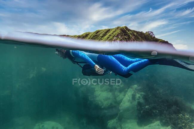 Mujer en traje de buceo buceo bajo el mar - foto de stock