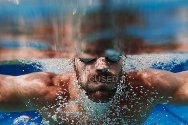 Плавець пірнає під водою в басейні. — стокове фото