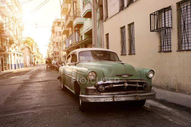 Cuba, La Habana, La Habana, Coche vintage verde pastel estacionado a lo largo de la calle de la ciudad al atardecer - foto de stock