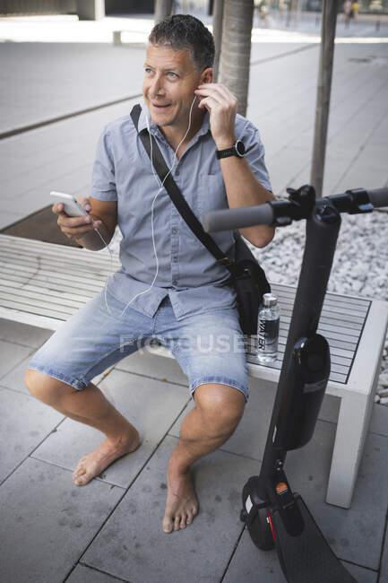 Hombre maduro escuchando música a través de auriculares mientras está sentado en el banco - foto de stock