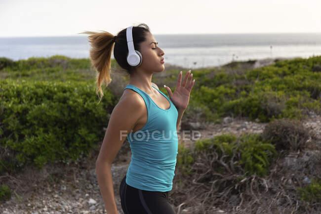 Молода латинка слухає музику під час бігу біля моря. — стокове фото