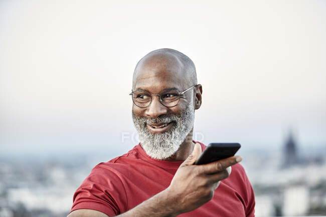 Smiling bald man talking through smart phone while looking away at building terrace during sunset — Stock Photo