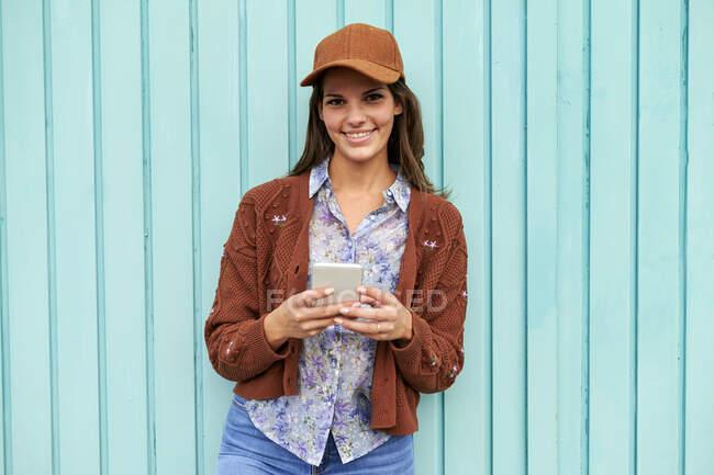Mulher sorridente mensagens de texto no telefone celular, enquanto em pé contra a porta de metal azul — Fotografia de Stock