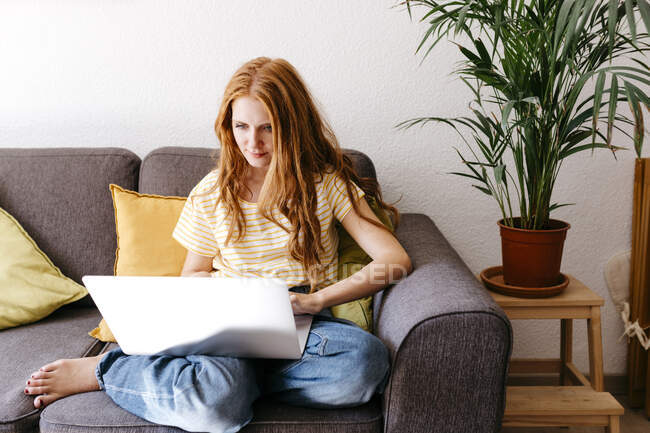 Молода жінка користується ноутбуком, сидячи вдома на дивані. — стокове фото