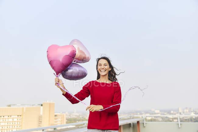 Mujer madura sosteniendo globo en forma de corazón mientras está de pie en la terraza del edificio contra el cielo despejado - foto de stock