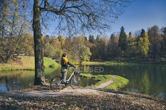 Mittlere erwachsene Frau blickt auf Ansicht, während sie Fahrrad im öffentlichen Park hält — Stockfoto