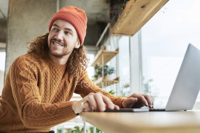 Sonriente hombre hipster mirando hacia otro lado mientras se utiliza el ordenador portátil en casa - foto de stock