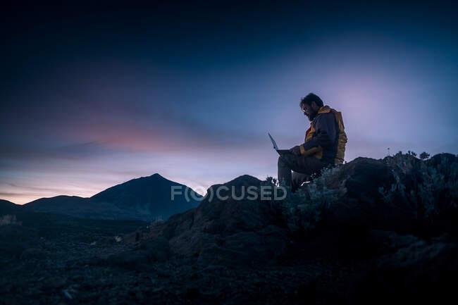 Man using laptop while sitting on rock at El Teide National Park, Tenerife, Spain — Stock Photo