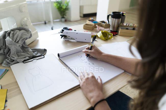 Young female creative designer sketching design in book at studio — Stock Photo
