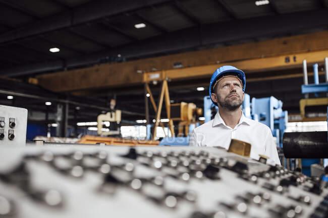 Задумчивый бизнесмен смотрит вверх, стоя на заводе — стоковое фото
