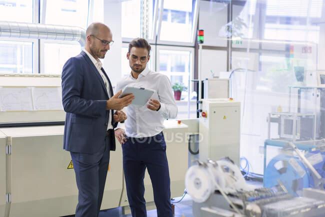 Довірливі чоловіки обговорюють через цифрову табличку, стоячи проти машин на заводі. — стокове фото