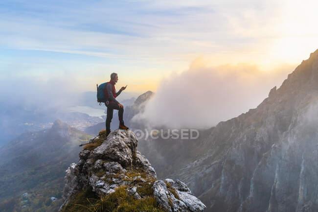 Excursionista pensativo usando un teléfono inteligente en el pico de la montaña durante el amanecer en los Alpes bergamascos, Italia - foto de stock