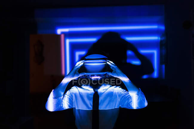 Man holding virtual glasses while standing in blue light reflection at home during pandemic — Stock Photo