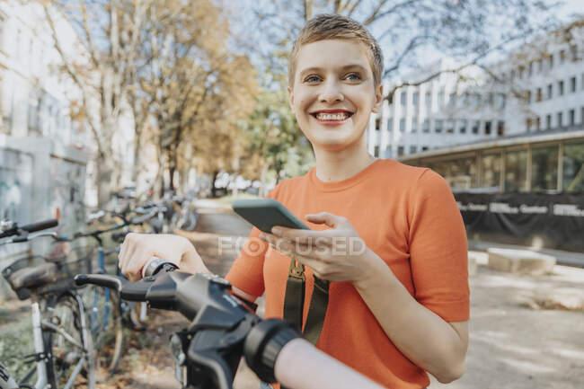 Улыбающаяся женщина с помощью смартфона, стоя на электроскутере в солнечный день — стоковое фото
