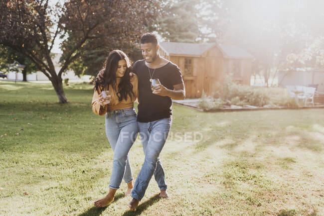 Чоловік і жінка тримають келих, ходячи на подвір