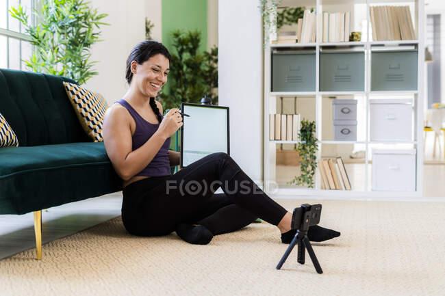 Influencer femminile che mostra tablet grafico mentre la registrazione video sulla fotocamera a casa — Foto stock