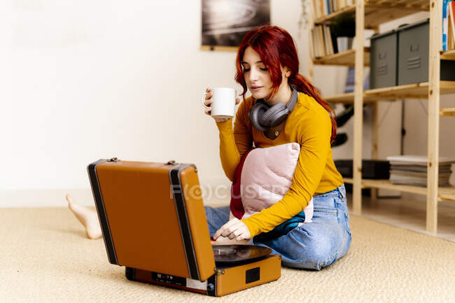 Junge Frau trinkt Kaffee, während sie Plattenspieler zu Hause benutzt — Stockfoto