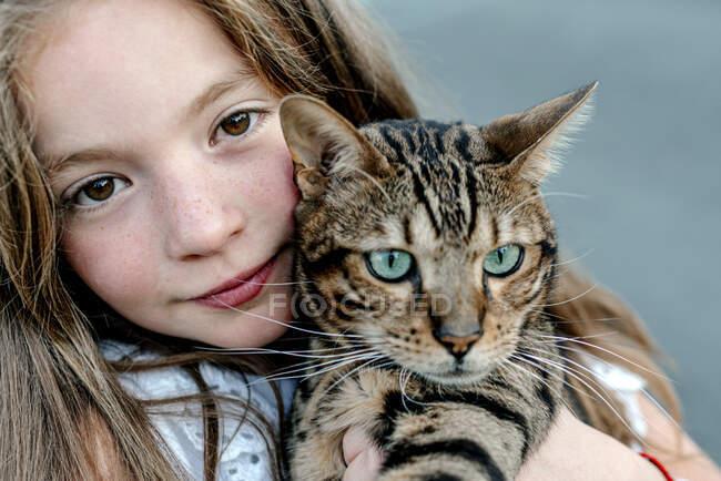 Linda chica llevando gato en día soleado - foto de stock