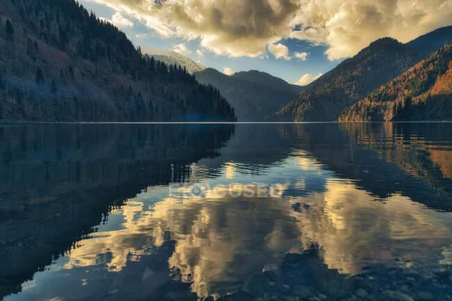 Clouds and surrounding mountains reflecting in Lake Ritsa at dusk, Abkhazia, Georgia — Stock Photo