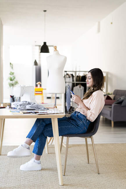 Young female designer using smart phone while sitting on chair at studio — Stock Photo