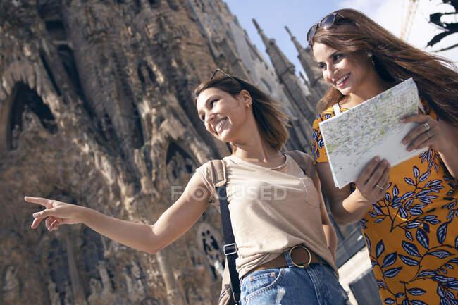 Donna che punta in piedi con un amico contro la Sagrada Familia a Barcellona, Catalogna, Spagna — Foto stock