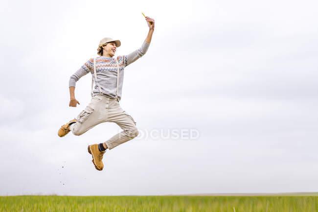 Joven tomando selfie a mitad de salto - foto de stock